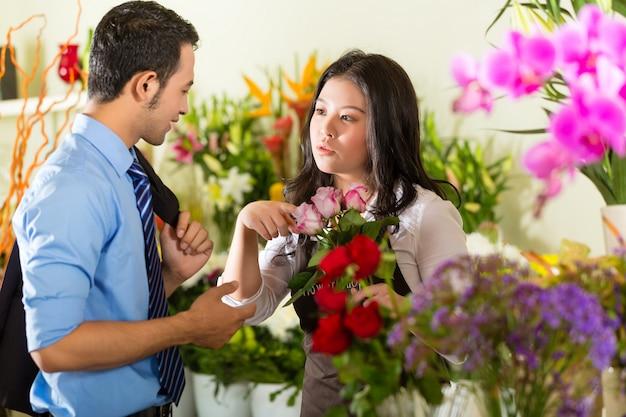 Продавщица и покупатель в цветочном магазине