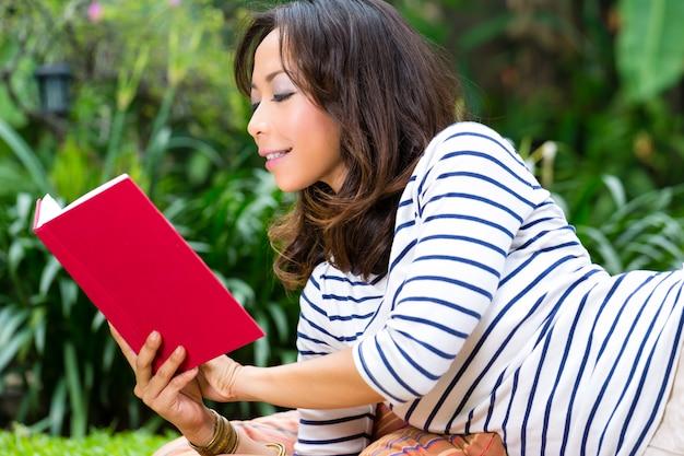 本を読んで庭で自宅でアジアの女性