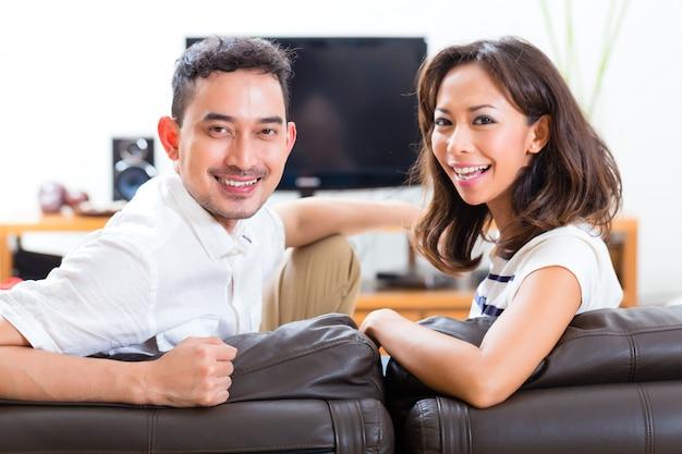 Азиатская пара дома в своей гостиной