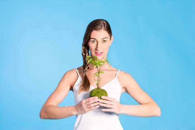 小さな木を保持している若い女性
