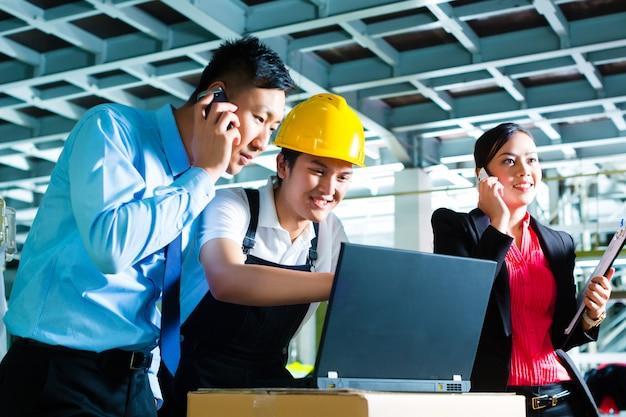 労働者または生産管理者と顧客サービス、織物工場でラップトップを見て、電話で助けます