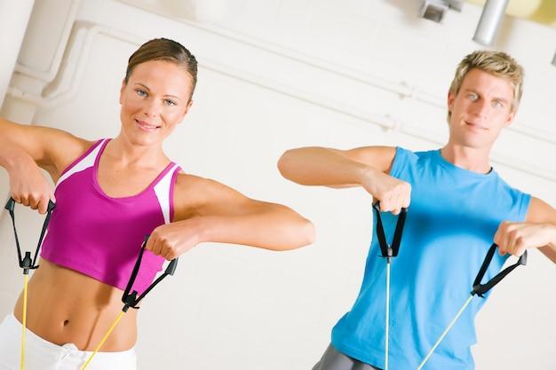 Пара занимается тренировкой в тренажерном зале