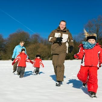 雪の中で実行している家族