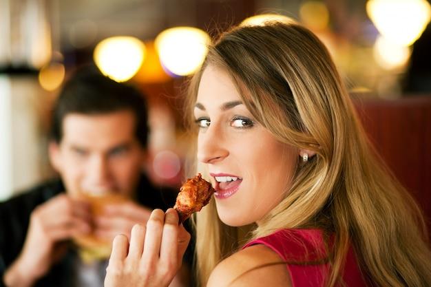 Пара в ресторане едят фаст-фуд