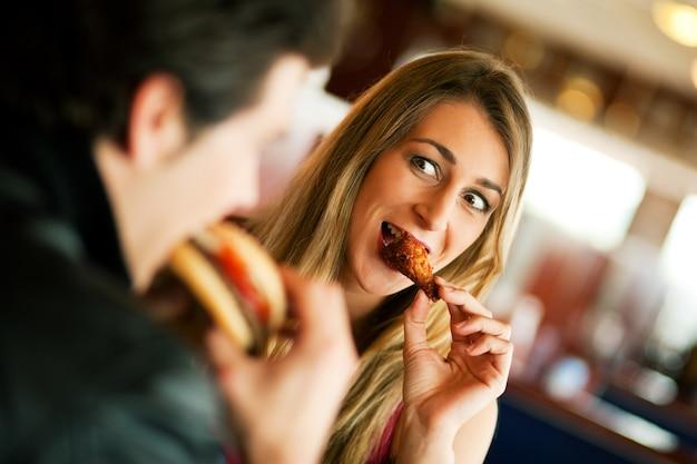ファーストフードを食べるレストランのカップル