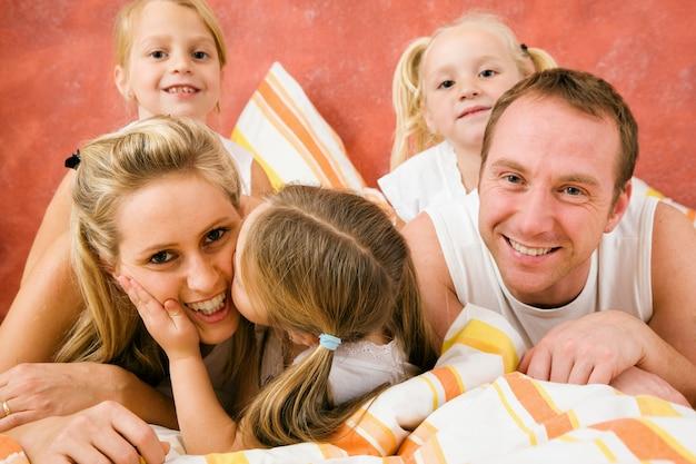 ベッドで家族、小さなキス