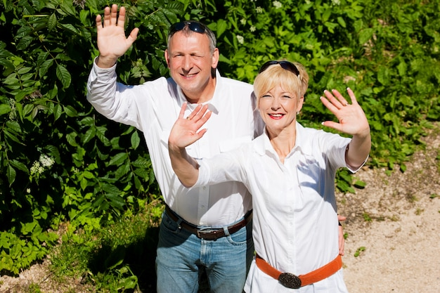 Счастливая пара старших на открытом воздухе, размахивая руками