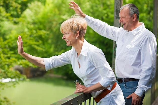 Счастливая пара старших на мосту, размахивая руками