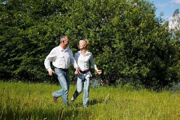 牧草地で実行されている年配のカップル