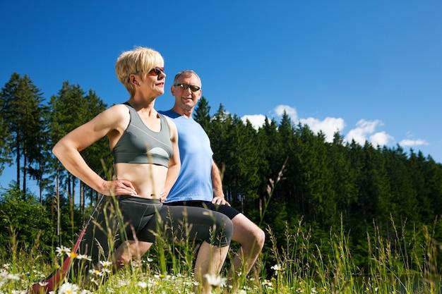 Пожилая пара занимается спортом на открытом воздухе