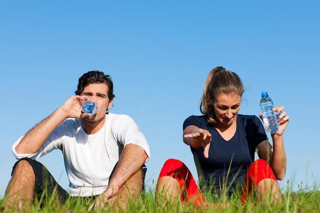 ジョガーカップル休憩と水を飲む