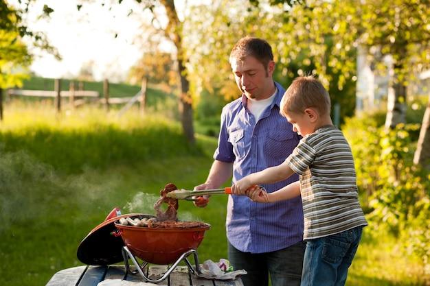 Семья устраивает барбекю в своем саду