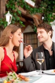 レストランでロマンチックなデートをカップルします。