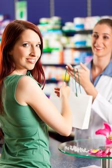 Женский фармацевт в своей аптеке с клиентом