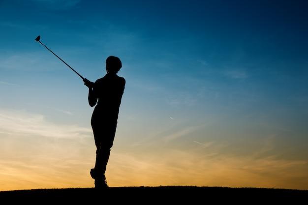 日没時のシニア女性ゴルフプレーヤー