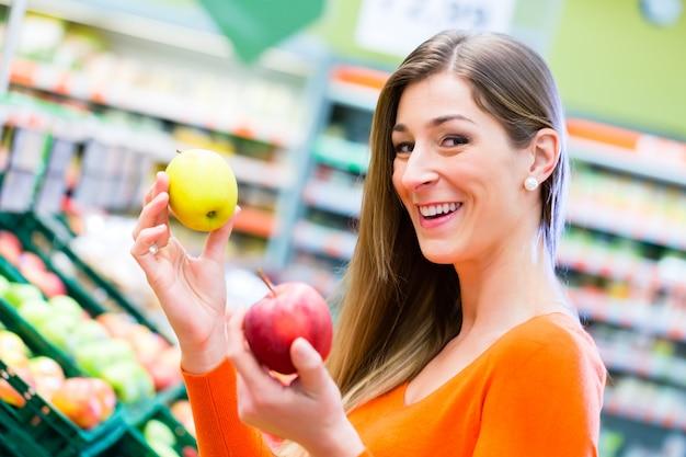 Женщина выбирая фрукты в супермаркете