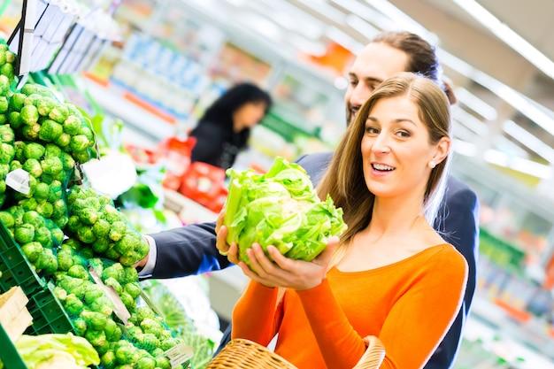 スーパーで食料品を買うカップル