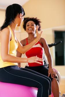 Две женщины с фитнес-мячом в тренажерном зале