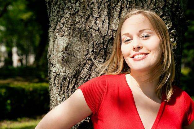 Девушка улыбается с деревом в спине