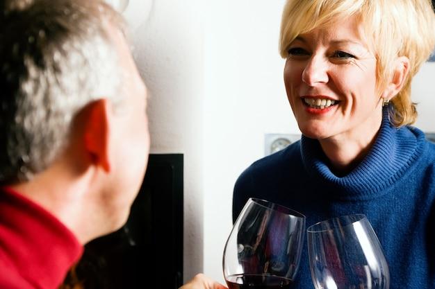 赤ワインを飲む年配のカップル