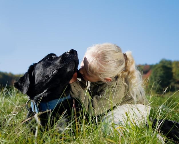 Девушка обнимает черную собаку
