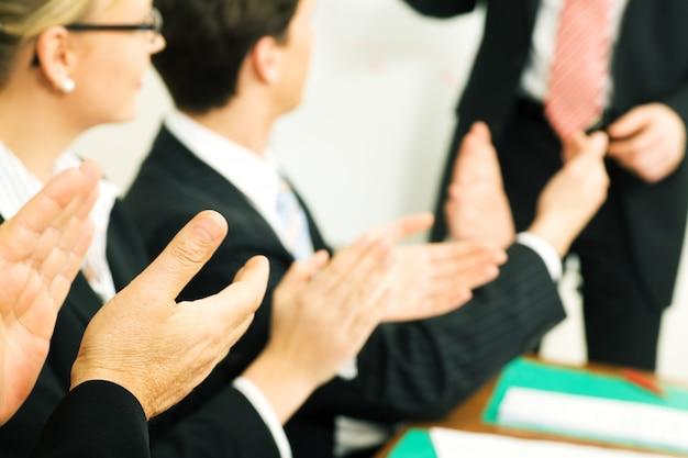 会議で拍手するビジネスマン