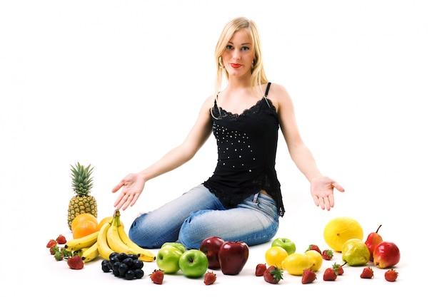 Женщина показывает много фруктов