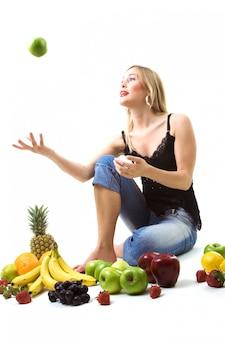 Девушка играет с зеленым яблоком