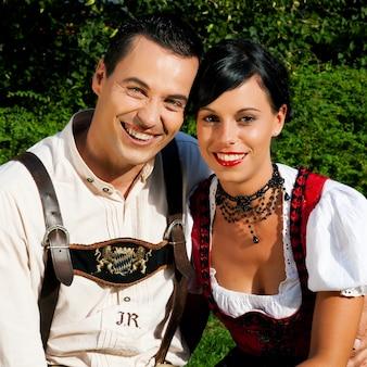 夏の伝統的なバイエルンのドレスのカップル