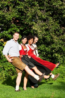 Группа из четырех друзей в баварской одежде танцы