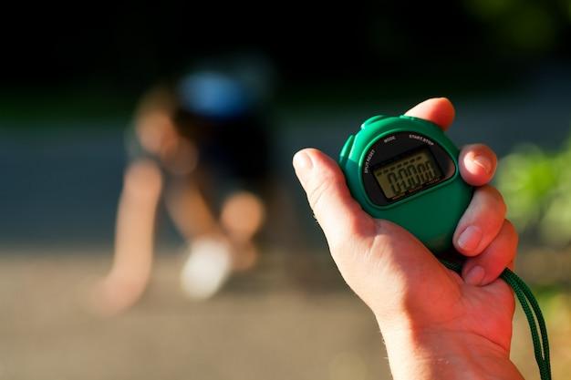 Тренер, измеряющий время бегуна