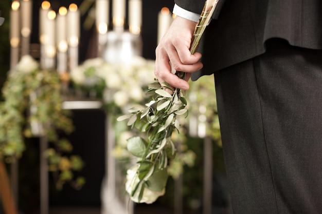葬儀で白いバラを持つ男