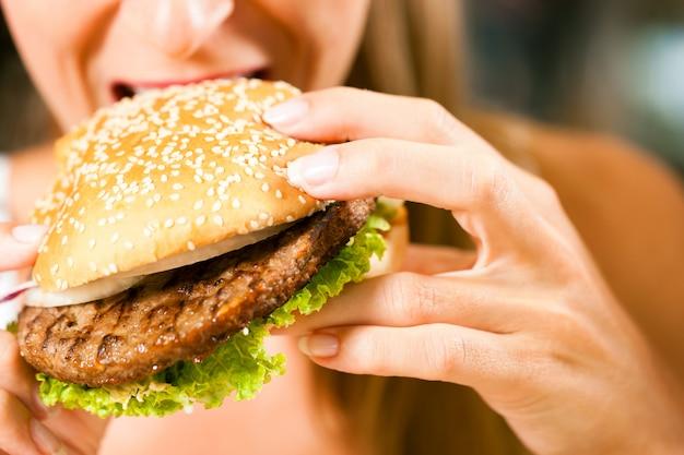 ハンバーガーを食べるレストランの女性