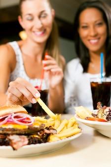 Две женщины едят гамбургер и питьевую соду