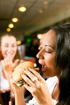 Друзья едят фаст-фуд в ресторане