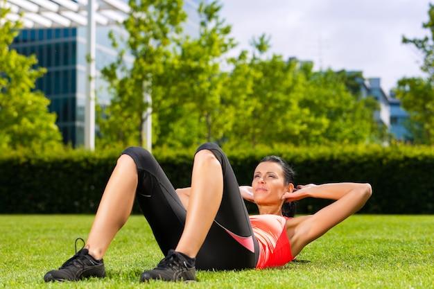 都市スポーツ-草の上のウォーミングアップの女性