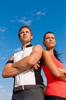 カメラの前でポーズをとってスポーツ服装の若いカップル