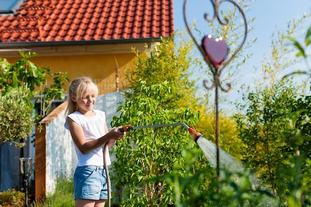 庭の植物に水をまく笑顔の女の子