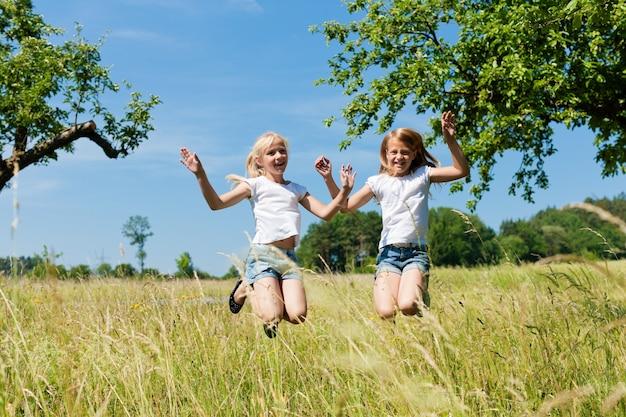 日当たりの良い牧草地でジャンプ幸せな子供