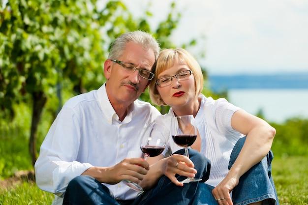中高年カップル、自然の中でワインを飲む