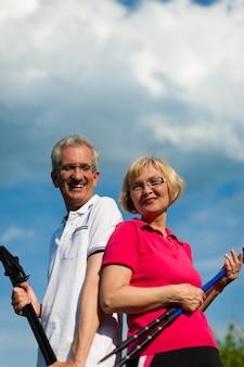夏にノルディックウォーキングをしている幸せな成熟したまたはシニアカップル