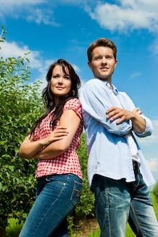 Пара в фруктовом саду позирует со скрещенными руками