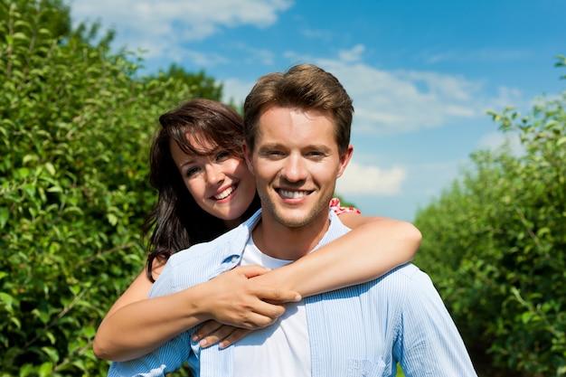 陽気な果樹園でポーズをとるカップル