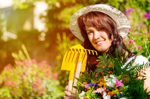 太陽に照らされた庭の花を持つ女性の庭師