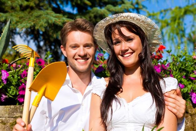 太陽に照らされた花の庭でガーデニングツールと幸せなカップル
