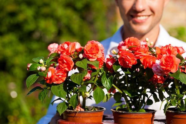 バックグラウンドでそれらを保持している男と鉢植えの花のクローズアップ