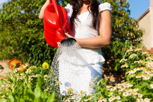 赤いじょうろで花に水をまく女性