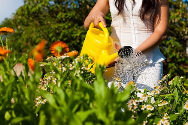 黄色の水まき缶で花に水をまく女性