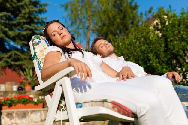 太陽の下でデッキチェアで休んでいるカップル