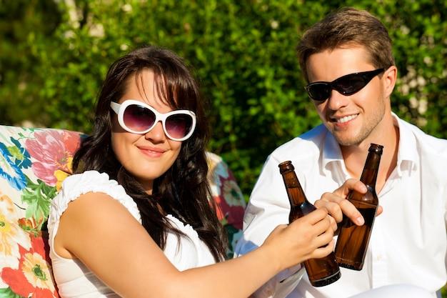 太陽の下でビールで祝う笑顔のカップル